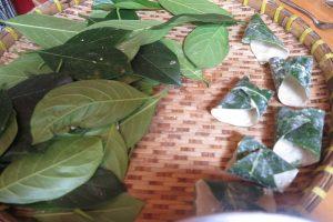 Cuộn bánh lá mít lại sau khi đã dàn đều bột.
