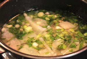 Cho thêm hành lá và rau mùi vào nồi canh và tắt bếp.