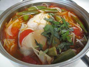 Cho rau thơm vào canh cá nấu và tắt bếp